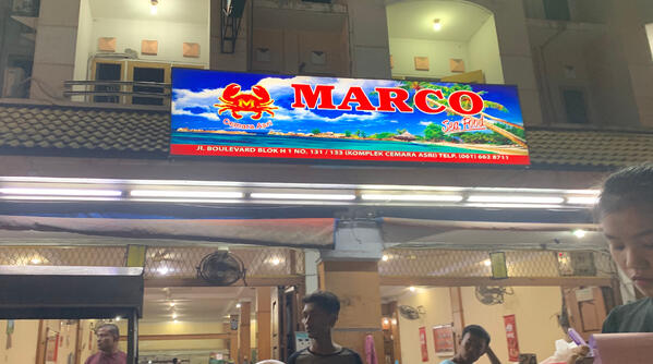 "Image shows a restaurant shopfront featuring a ""Marco"" signboard"
