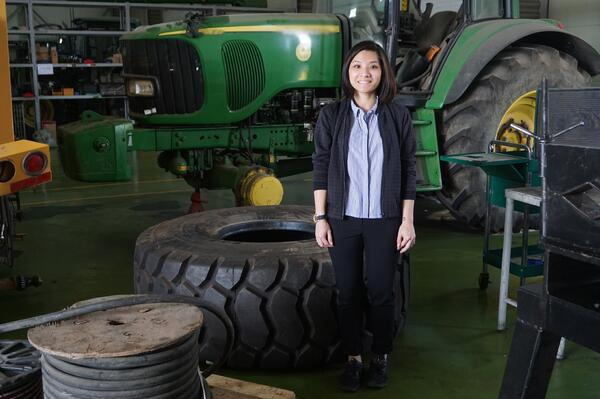 Image shows a woman standing in front of a big tractor and a huge tire