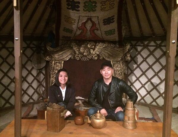 Image shows a woman and a man sitting inside a hut